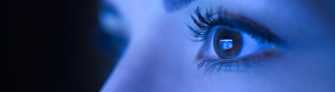 Close-up of beautiful young woman eyes looking at monitor, working with computer, laptop. Monitor blue light is reflected in her eyes.