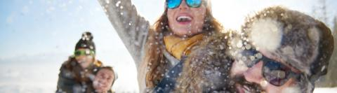 Woman with snow in hands outside, wearing sunglasses in winter