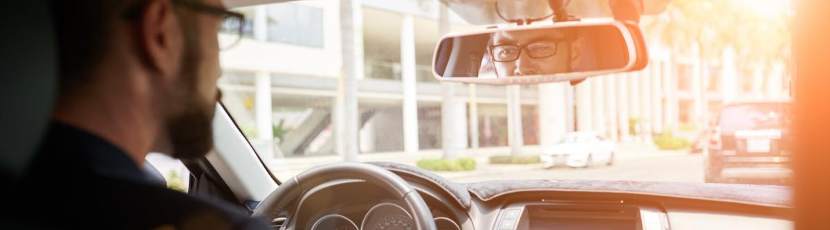 Young businessman driving to work, view over the shoulder, driving with glasses, vision screening or requirements for drivers license concept